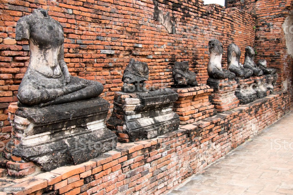 Ancient broken buddha statue with red brick background in temple at Ayutthaya, Thailand stock photo