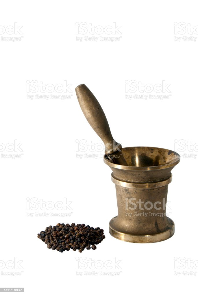 ancient bronze mortar and a handful of black pepper peas on a white background stock photo