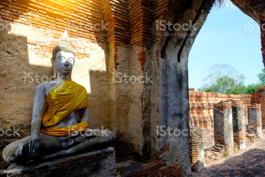 Ancient Buddha and old brick wall on ancient monuments that are over 200 years old. Wat Nakhon Luang Tample,Prasat Nakhon Luang public domain or treasure of Buddhism in  Ayutthaya, Thailand stock photo