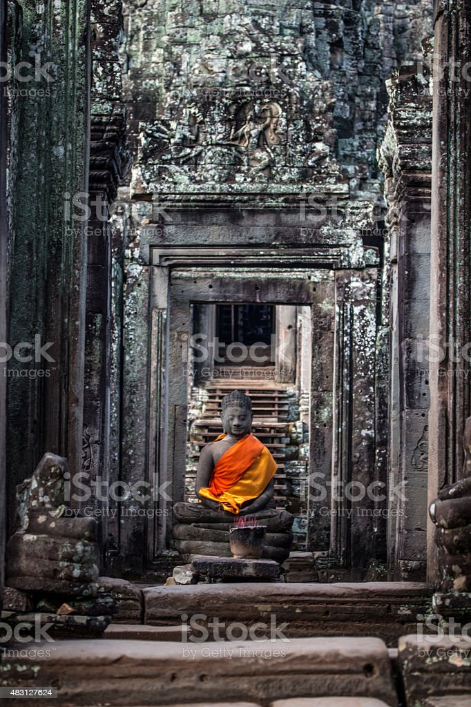 Ancient Buddha Statue in middle of ancient archway of BayonTemple stock photo