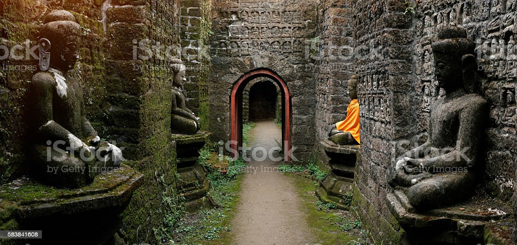 Ancient Buddha statue in orange cover stock photo