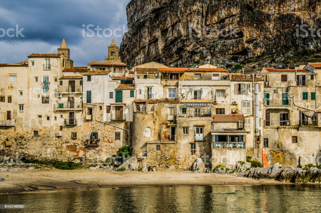 ancient buildings surrounded by sea and rock in Cefalu stock photo