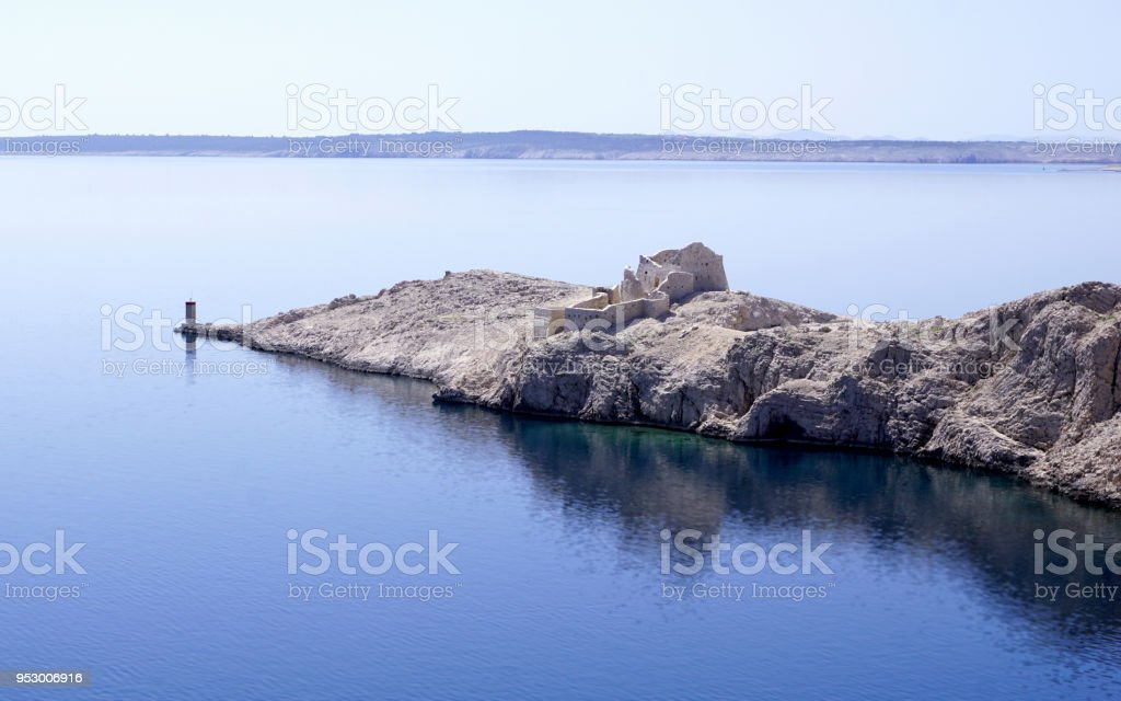 Ancient Byzantine town of Fortica, ruins on the edge of the island of Pag, Croatia, with a turquoise blue reflection in the sea stock photo