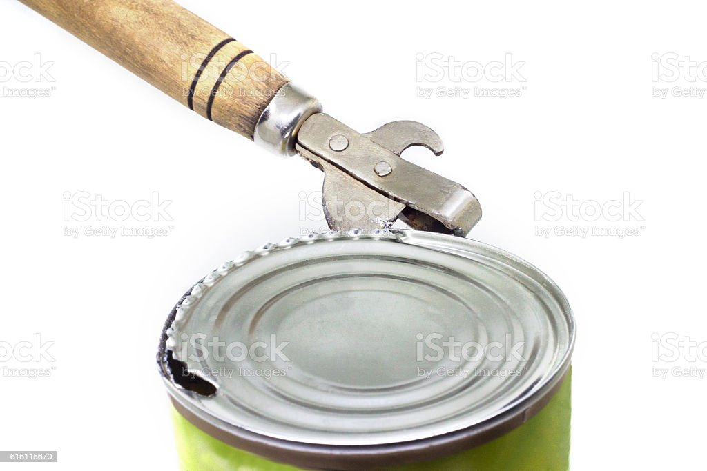 Ancient can opener opening a can - foto de stock