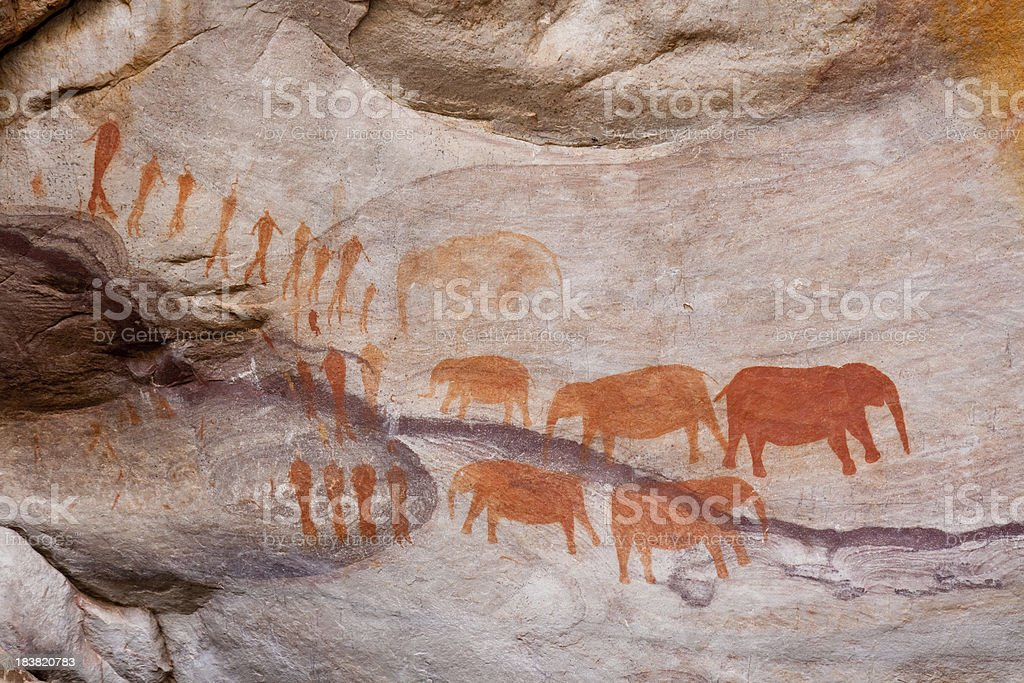 """Ancient cave painting of humans and elephants """"Cave paintings or rock art created more than 1,000 years ago in a cave at Stadsaal in the Cederberg mountains, South Africa, by the original Bushman inhabitants of the region."""" African Elephant Stock Photo"""