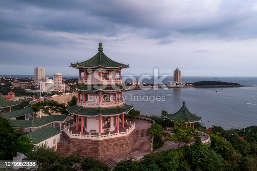 istock Ancient Chinese architecture with new qingdao china skyline by night 1279952338