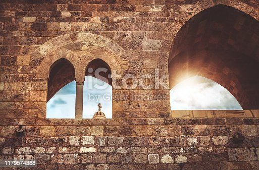Ancient church in Lebanon, amazing architecture, place of worship, the cross on the dome of the church in bright sunlight is visible in the windows of the fortress
