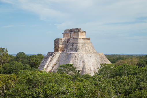 istock Ancient city in the jungle. Mayan temple Uxmal archeological site, ruins in Yucatan. Pyramid of the Magician (Piramide del adivino) in ancient Mayan city Uxmal, Mexico 915151906
