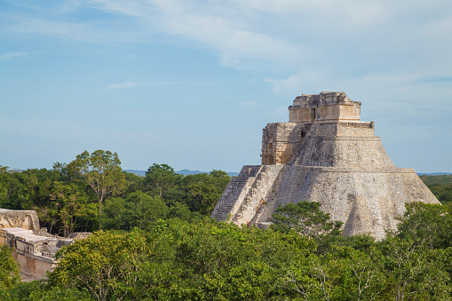 istock Ancient city in the jungle. Mayan temple Uxmal archeological site, ruins in Yucatan. Pyramid of the Magician (Piramide del adivino) in ancient Mayan city Uxmal, Mexico 915151914