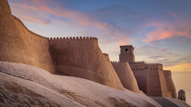 oude stadsmuren van khiva oezbekistan in zonsondergang twilight - karavanserai stockfoto's en -beelden