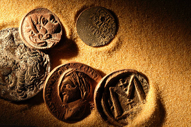 ancient coins laying in golden sand - roman stock photos and pictures