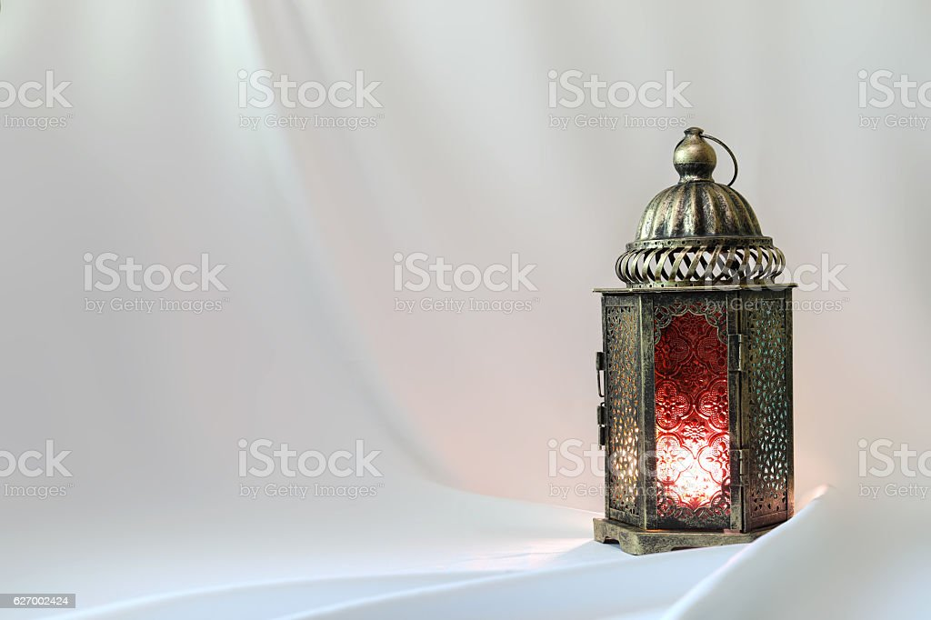 Ancient colored lantern on white satin stock photo