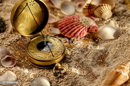 490314373 istock photo Ancient compass on the sand with seashells 1019388446