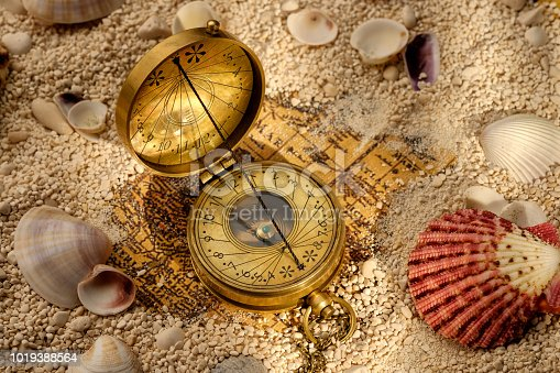 490314373 istock photo Ancient compass on the sand with seashells 1019388564