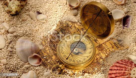490314373 istock photo Ancient compass on the sand with seashells 1019388578