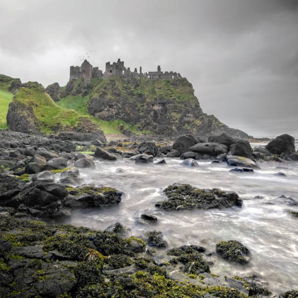 oude dunluce castle op een klif, ierland - stadsdeel stockfoto's en -beelden
