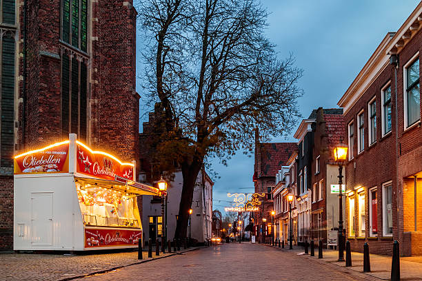 ancient dutch street with christmas decoration and small booth - oliebollen stockfoto's en -beelden