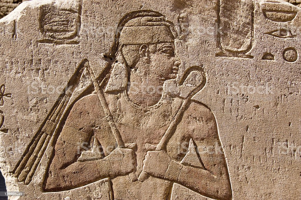 Ancient Egyptian carving of Pharaoh with flail and sceptre stock photo