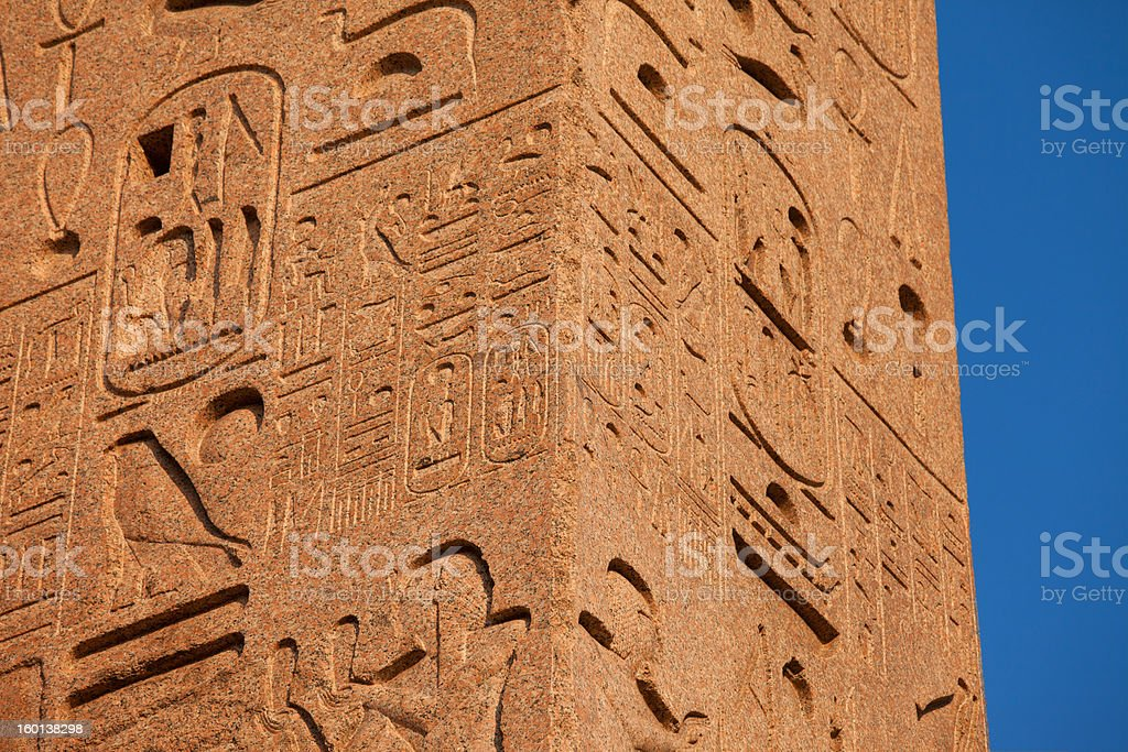 Ancient egyptian hieroglhyps on red granite column, blue sky royalty-free stock photo