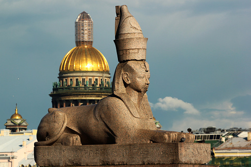 Saint Petersburg, Russia - July 4, 2017: Ancient Egyptian Sphinx from Thebes at the Universitetskaya Embankment with Saint Isaac Cathedral in background.