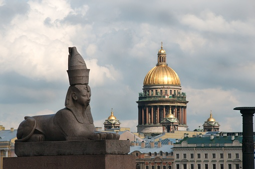 Ancient Egyptian sphinx of pharaoh Amenhotep III with the Saint Isaac's Cathedral in the background. Universitetskaya Embankment in Saint Petersburg