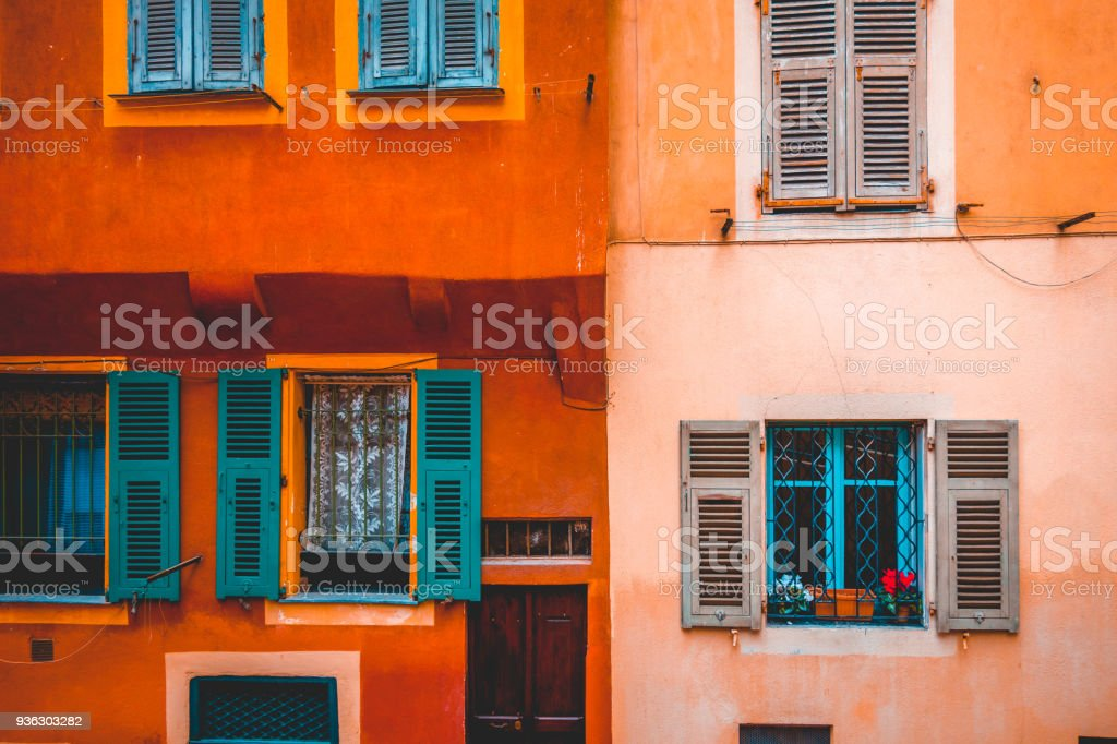 ancient facade in orange and rose colors with green windows stock photo