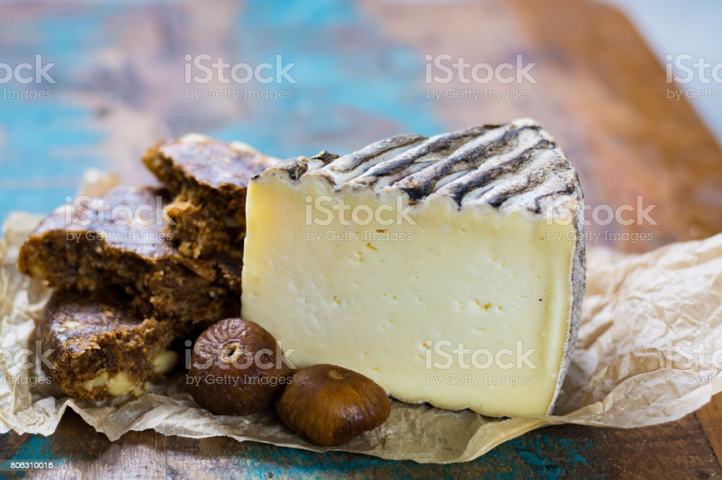 Ancient french cheese Tomme de Montagne and dried figs with figs bread stock photo