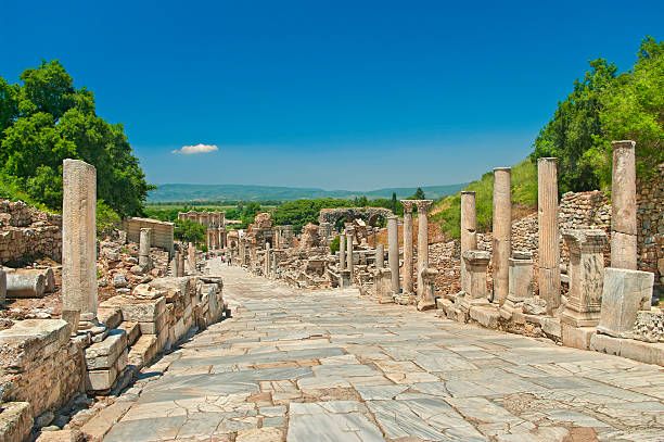 ancient greek alley with columns marble alley with columns leading to the Celsus Library in ancient greek city of Ephesus with mountains and clear blue sky at background with single small cloud over the Celsus Library, Turkey celsus library stock pictures, royalty-free photos & images
