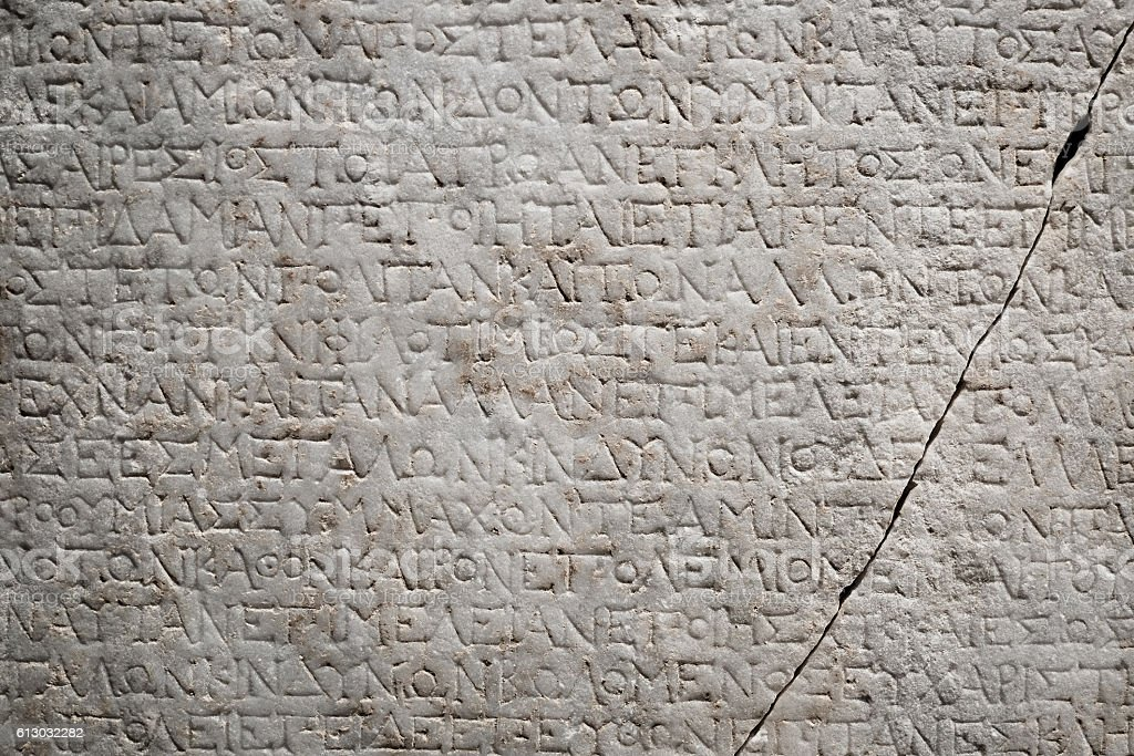 ancient greek engraved writing on a marble stone stock photo