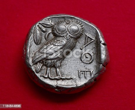 Ancient Greek coin  - from my own coin collection and over two thousand years old. An Athenian Tetradrachm from after 499 BC, showing the owl of Athena and the Ancient Greek letters for Athens  - also an olive twig and crescent moon
