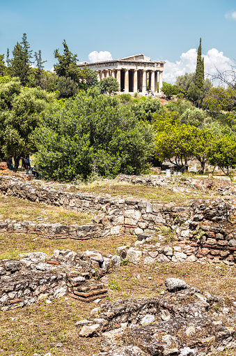 Ancient Greek ruins in Agora, Athens, Greece. Temple of Hephaestus, landmark of Athens in distance. Vertical scenic view of remains of famous classical Athens culture. Travel and history concept.