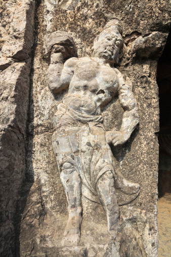 ancient hercules statue on the rocks in longmen grottoes,China
