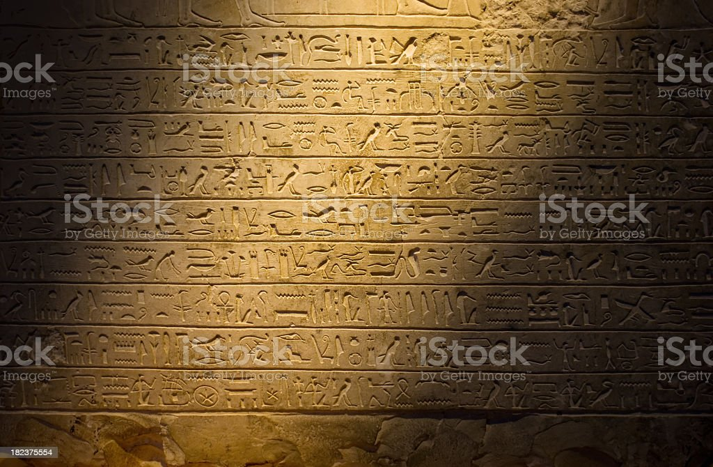 Ancient hieroglyphics dimly lit stock photo