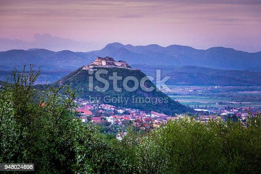 Color image depicting the ancient citadel fortress in Deva, a small town in the Transylvania region of Romania. It is twilight and the sky and cloudscape has a pink glow. In the foreground is lush green foliage, and the citadel, and surrounding town of Deva, rises up in the distance. Room for copy space.