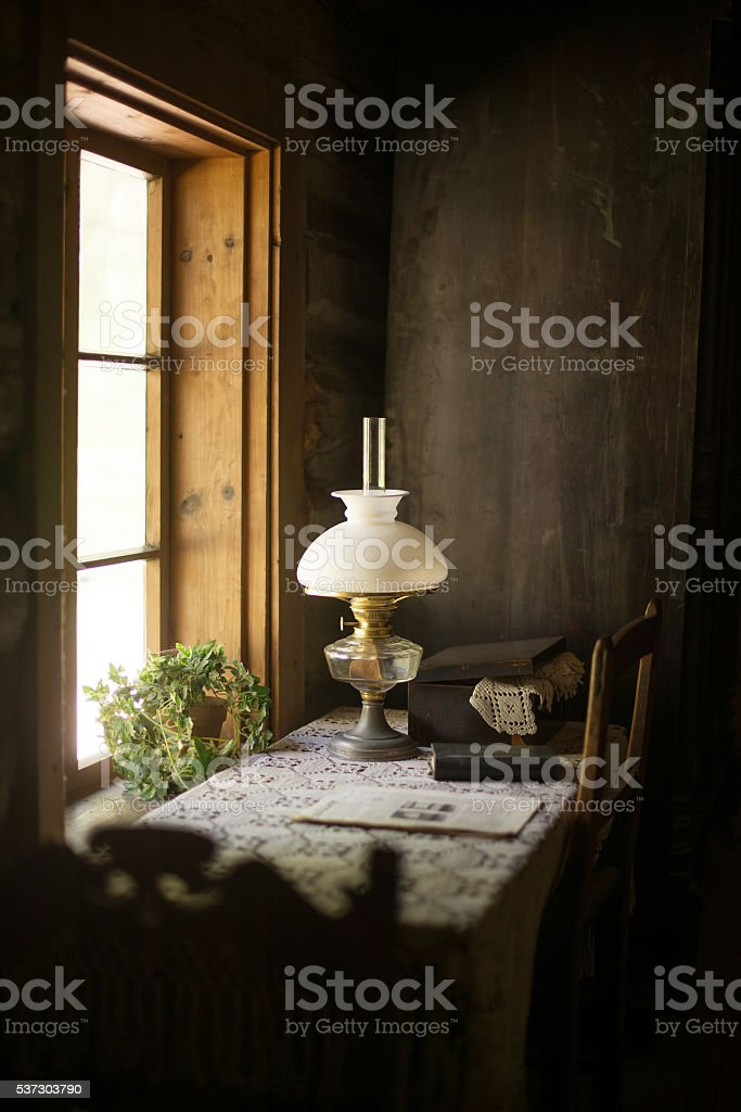 Ancient house interior with lamp and table. stock photo