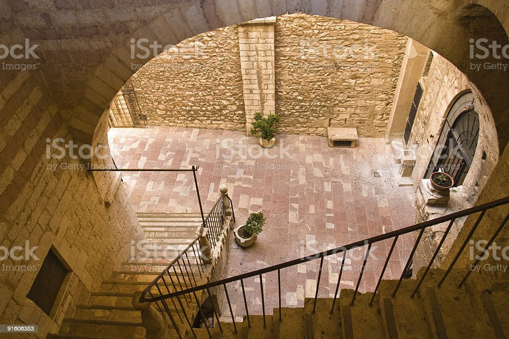 Ancient Italian courtyard with a staircase royalty-free stock photo