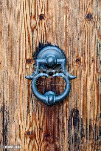 Ancient italian door knocker on old wooden brown background.
