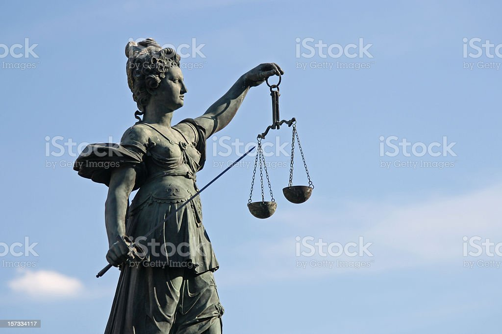 ancient Justicia statue with scale and sword royalty-free stock photo