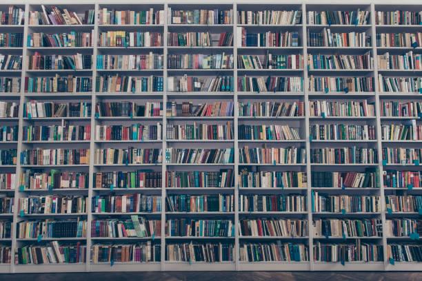 Ancienne bibliothèque design d'intérieur avec des étagères de livre gris en bois massif, pleins de littérature colorée, tomes, publications et plancher en bois - Photo