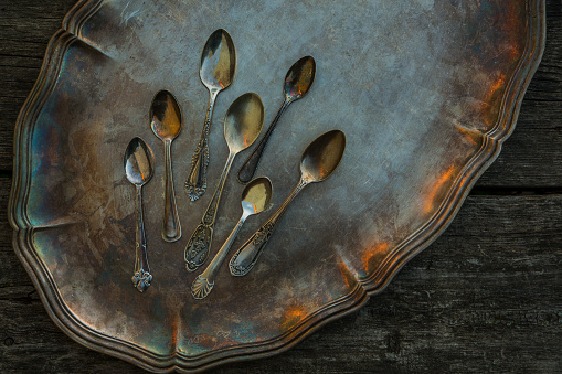 Ancient little spoons on a vintage silver platter, tray. Vintage cutlery, kitchen utensils as concept, idea on a wooden background.