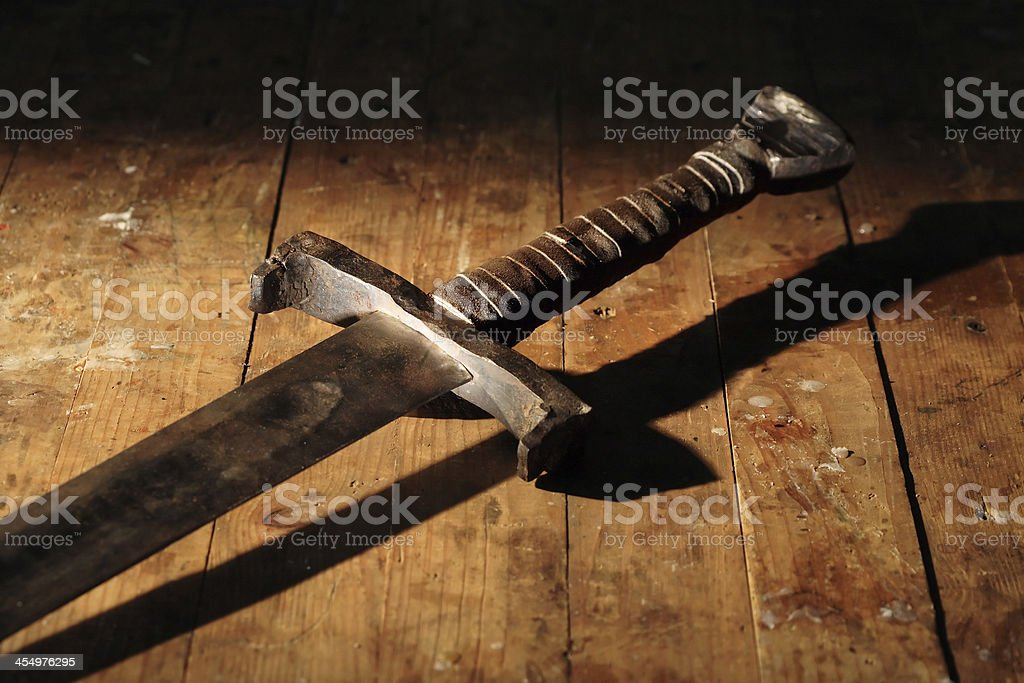 Ancient longsword on a rustic wooden floor stock photo