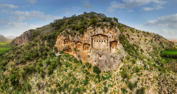 Ancient Lycian Rock Tombs of Dalyan, Mugla, Turkey Above the river's sheer cliffs are the weathered façades of Lycian tombs cut from rock, circa 400 BC. anatolia stock pictures, royalty-free photos & images