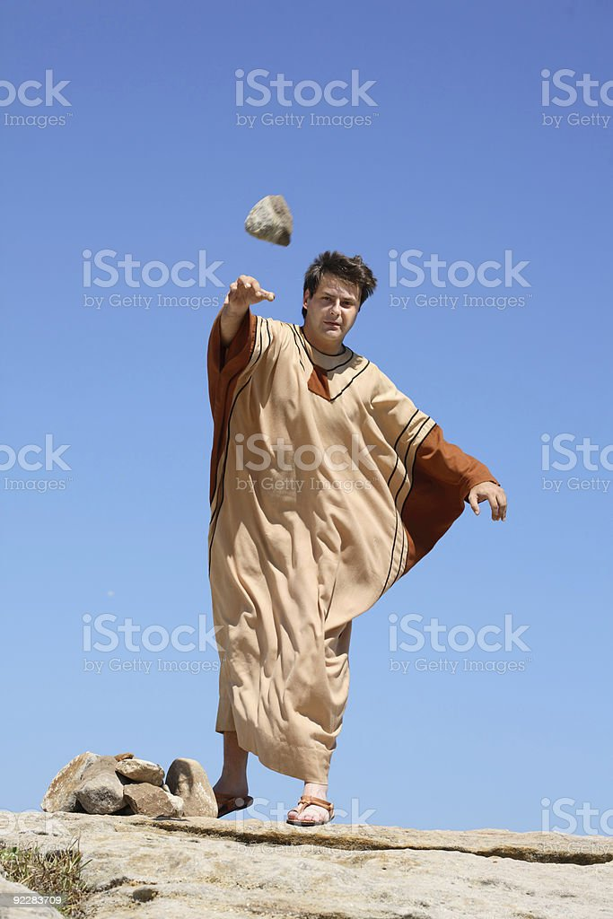 Ancient man casting a stone stock photo