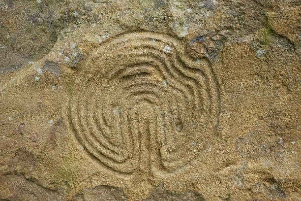 Ancient maze carved on rock A maze symbol carved on an ancient standing stone. new age music stock pictures, royalty-free photos & images