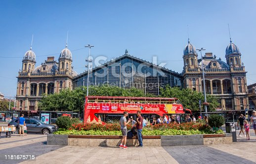Budapest, Hungary -August 29, 2019: Nyugati pályaudvar - Budapest's old western train station. Facade of the railway station building and tourists on the city street of Budapest. Bus tours in Hungary