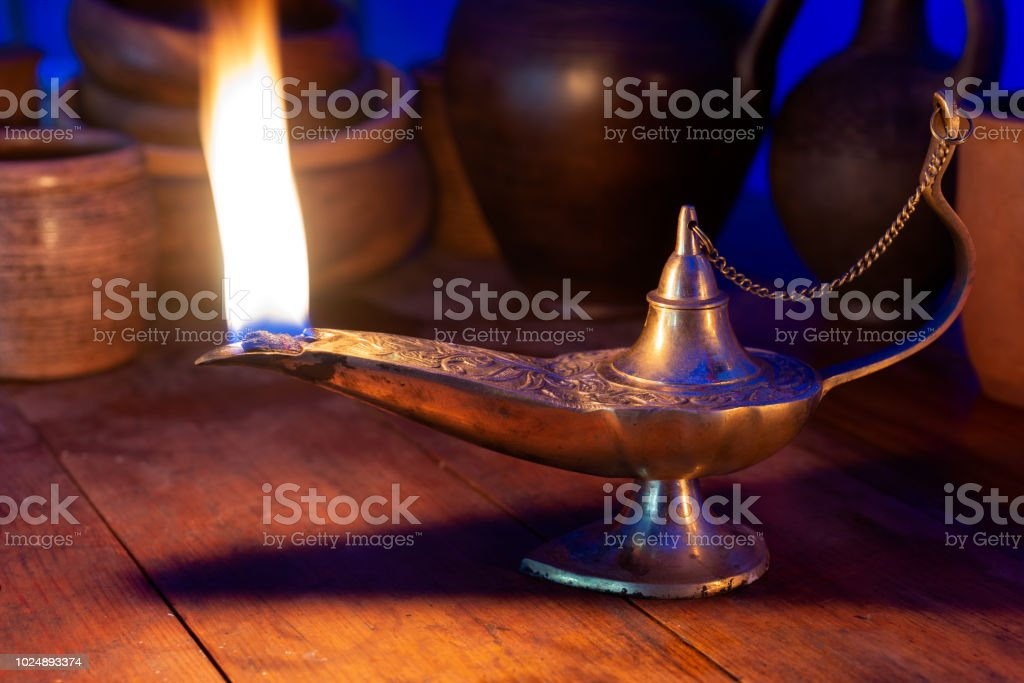 Ancient oil lamp burns on a wooden table стоковое фото