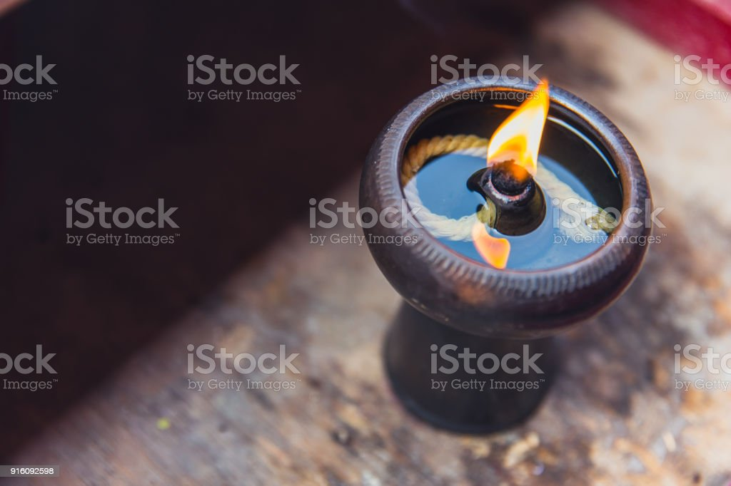 Ancient oil lamp made in clay on wood table stock photo