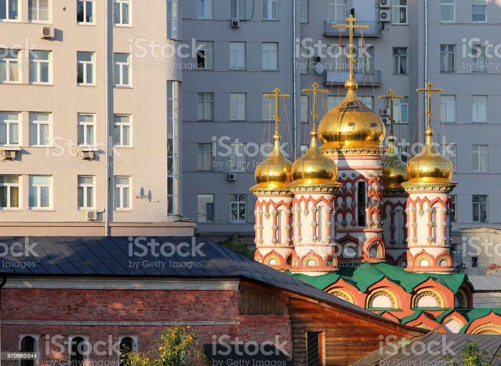 Ancient orthodox church on a background of a modern multistorey building in Moscow, Russia stock photo