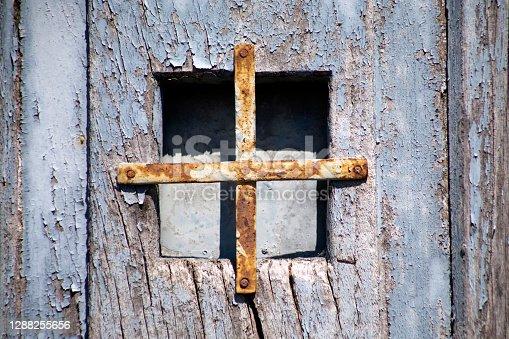istock Ancient peephole, blue wooden door peeling off. 1288255656