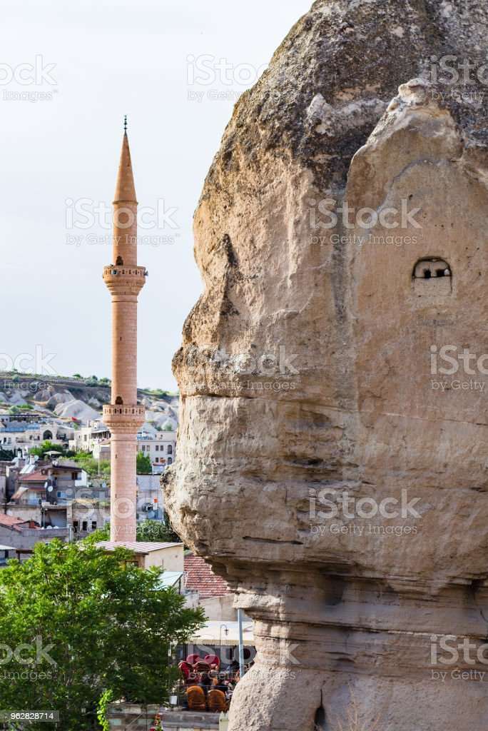 ancient rock-cut house and mosque in Goreme town - Foto stock royalty-free di Ambientazione esterna